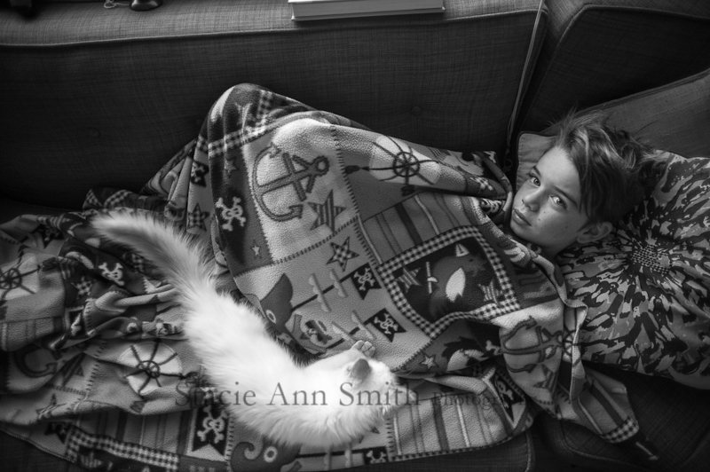 boy with his cat cuddling on couch, b&w photograph
