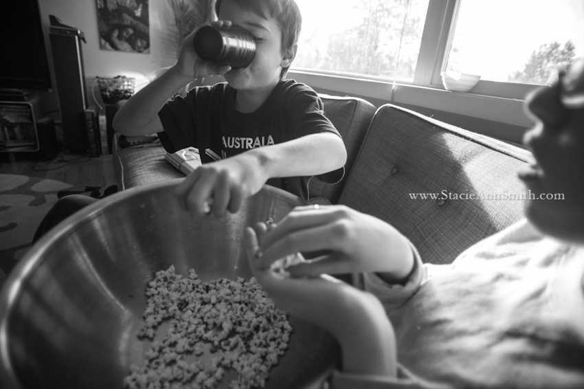 a b&w photograph of a kid eating popcorn while also drinking from his cup near Denver