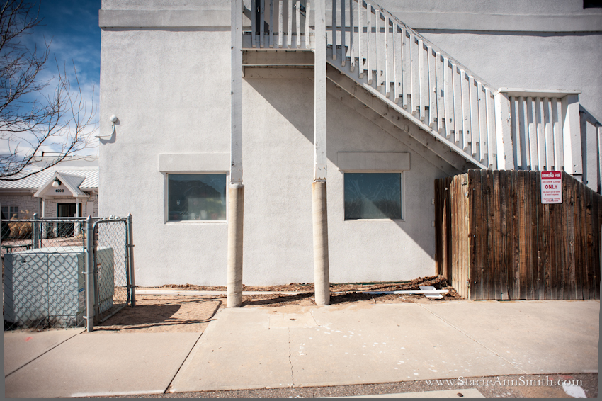 Color photograph of the side of a building, twin windows and twin poles, Fort Collins, Colorado